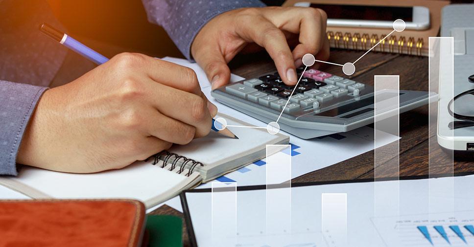 homem com a calculada e fazendo anotações demonstra a importância da revisão contábil